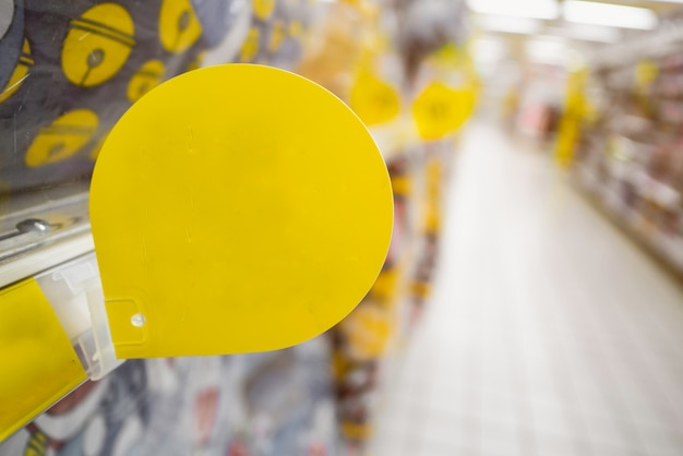 Derida sull'etichetta in bianco gialla di sconto sugli scaffali dei prodotti in supermercato Foto Premium
