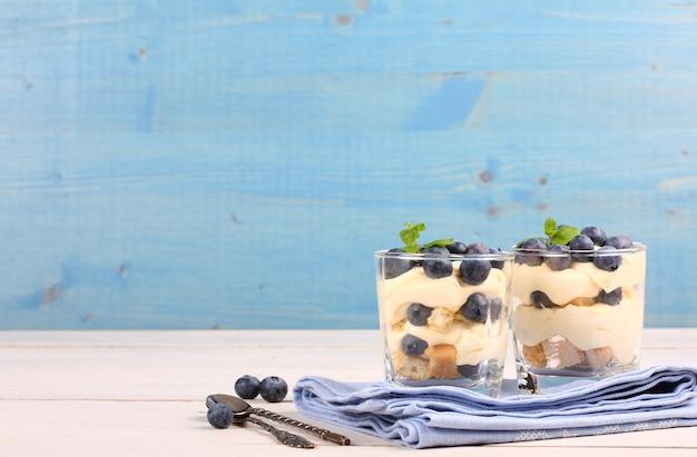 Deserto stratificato di mirtilli freschi con crema al mascarpone e biscotti in vetro Foto Premium