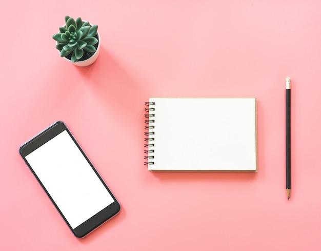 Design piatto mockup di posto di lavoro scrivania con taccuino in bianco, smartphone, caffè, cancelleria su colore pastello rosa con spazio di copia Foto Premium