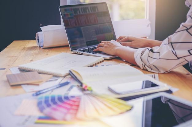 Designer che lavora con la grafica a colori sul computer portatile per presentare un nuovo progetto di grafica. Foto Premium