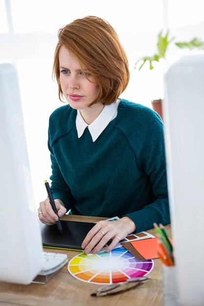 Designer hipster sorridente, seduto alla sua scrivania, su una tavoletta digitale Foto Premium