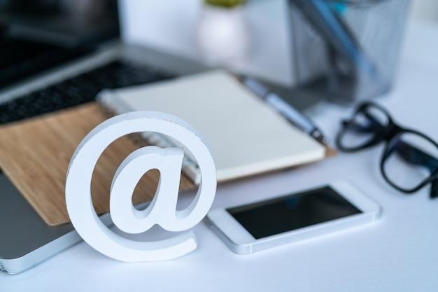 Desktop con blocco note, smartphone, occhiali e simbolo e-mail. Foto Premium