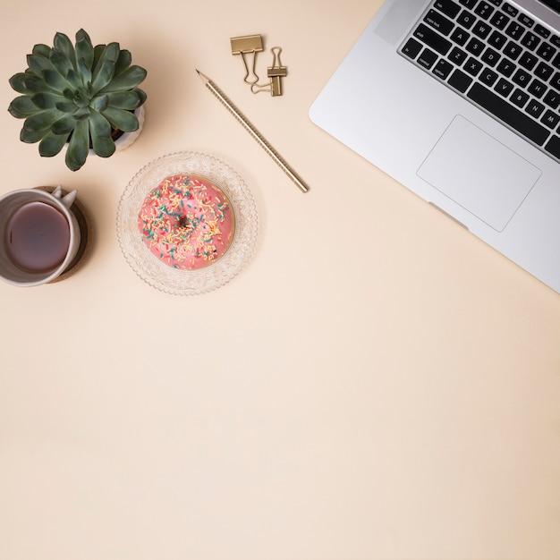 Desktop dell'ufficio con un laptop e altri elementi Foto Gratuite