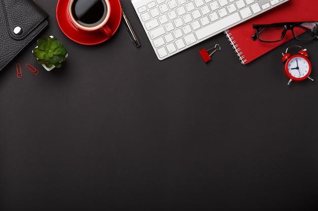 Desktop rosso dello spazio vuoto della tastiera dei punteggi del diario del fiore della sveglia del blocco note della tazza di caffè del fondo nero Foto Premium