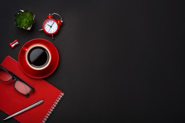 Desktop vuoto dello spazio del fiore rosso della sveglia del blocco note della tazza di caffè del fondo nero Foto Premium