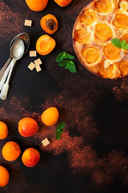 Dessert delizioso casalingo della frutta della torta dell'albicocca di estate. crostata di albicocche. torta di frutta. sfondo rustico scuro. vista dall'alto. copia spazio Foto Premium