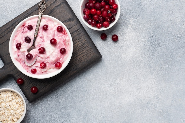 Dessert della ricotta dell'ostruzione e dei mirtilli rossi del yogurt su un piatto. tavolo in cemento grigio Foto Premium