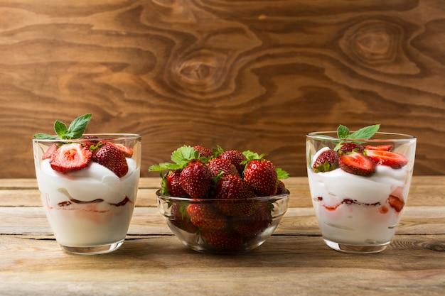 Dessert delle fragole con panna montata su fondo di legno rustico Foto Premium