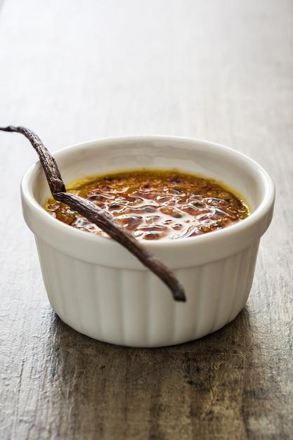 Dessert francese tradizionale della crema brulée con zucchero caramellato sulla cima, sulla tavola di legno Foto Premium