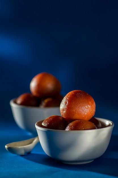 Dessert indiano: gulab jamun in una ciotola Foto Premium
