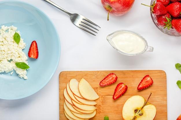 Dessert sano con ricotta e fragole nel piatto blu su una tovaglia bianca Foto Premium