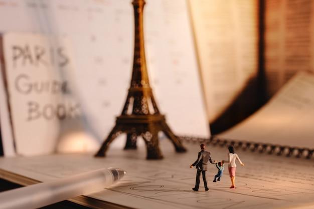 Destinazione da sogno per le vacanze. viaggia a parigi, in francia. una famiglia di turisti in miniatura che cammina alla torre eiffel e al calendario. tono caldo. stile vintage Foto Premium