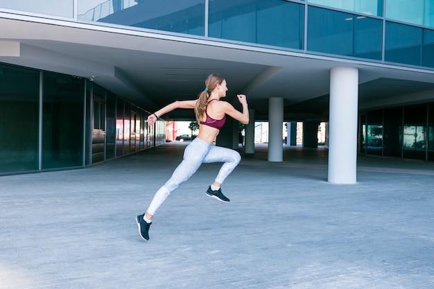 Determinata giovane donna che corre fuori dall'edificio Foto Gratuite