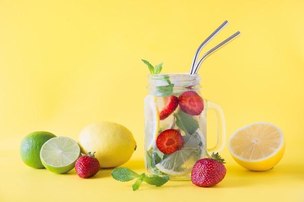 Detox acqua, limonata o mojito con limone, lime, fragola in barattolo su giallo Foto Premium