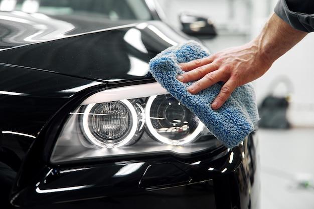 Dettagli dell'auto: l'uomo tiene in mano la microfibra e lucida la macchina Foto Premium