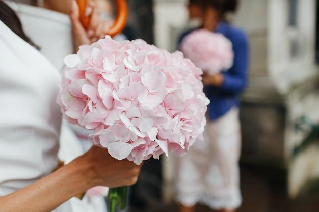 Dettagli di nozze la sposa tiene il tenero bouquet rosa tra le sue braccia. senza faccia Foto Gratuite