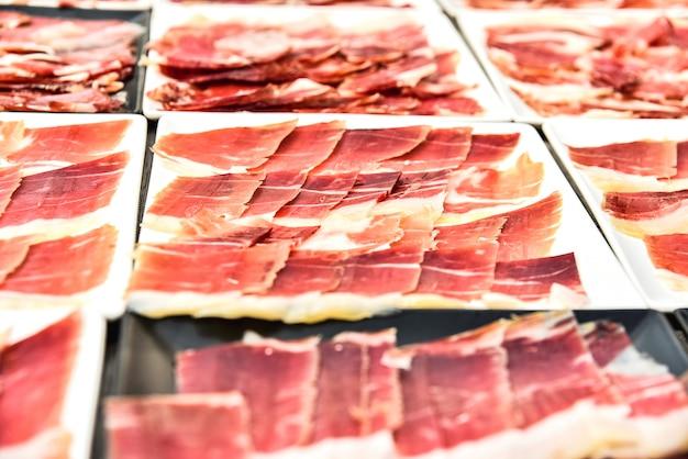 Dettaglia vari piatti di prosciutto serrano tagliato durante un evento. Foto Premium