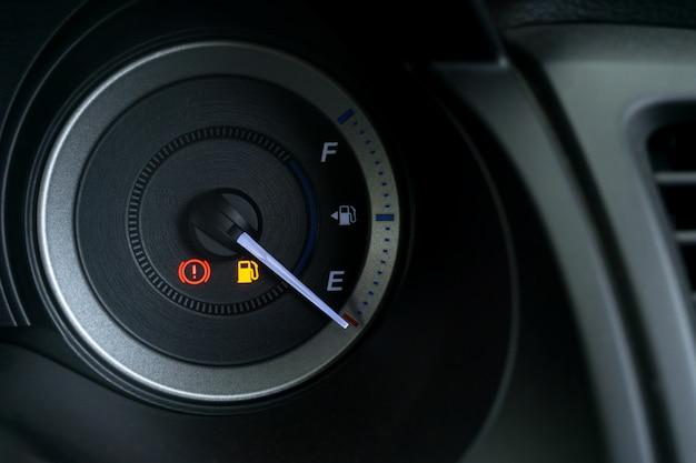 Dettaglio con gli indicatori di livello del carburante che mostrano e serbatoio vuoto sul cruscotto dell'auto Foto Premium