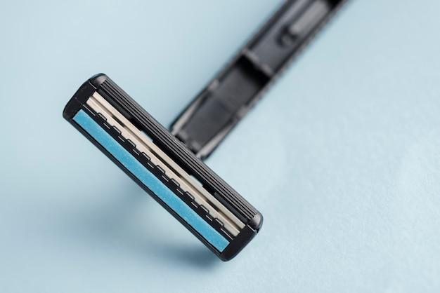 Dettaglio del rasoio nero usa e getta contro sfondo blu Foto Gratuite