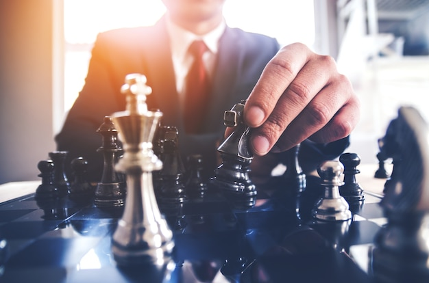 Dettaglio di una mano che fa la prima mossa in una partita a scacchi, spostando in avanti il campo di un pedone Foto Premium