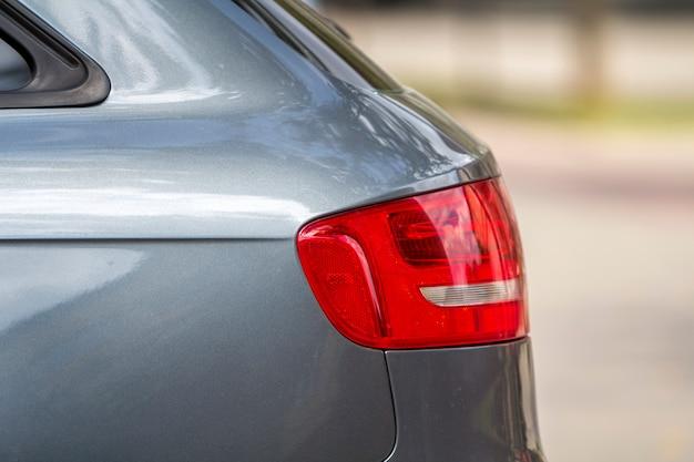 Dettaglio di vista laterale delle luci di arresto rosse dell'automobile d'argento lussuosa brillante Foto Premium