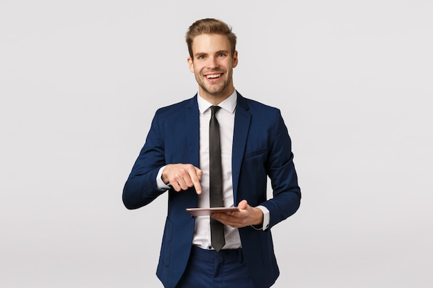 Devi vedere questo. imprenditore maschio elegante allegro in abito classico, cravatta, tenendo la tavoletta digitale e puntando lo schermo del gadget per mostrare al partner commerciale notizie fantastiche scritte sulla rivista online Foto Premium