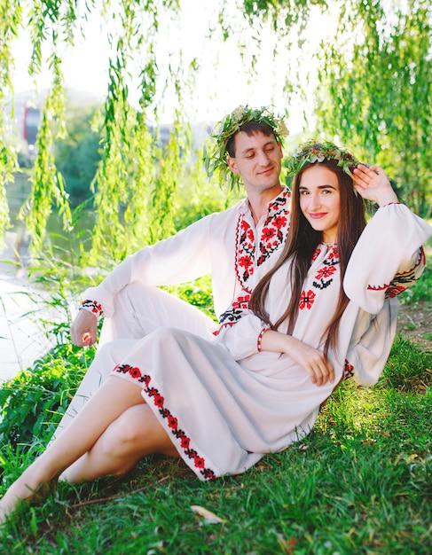 Di mezza estate. giovani coppie amorose in costumi slavi sulla riva del lago. festa slava di ivan kupala. Foto Premium