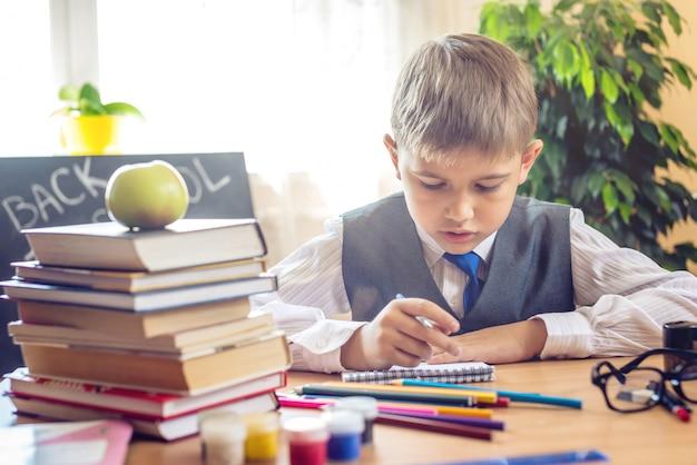 Di nuovo a scuola. bambino carino seduto alla scrivania in classe. il ragazzo sta imparando le lezioni Foto Premium