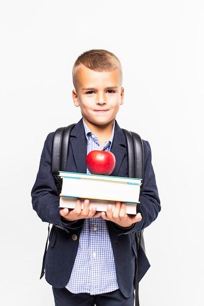 Di nuovo a scuola. libri, mela, scuola, ragazzo. il piccolo studente tiene i libri. piccolo bambino sorridente allegro contro la lavagna. concetto di scuola Foto Gratuite