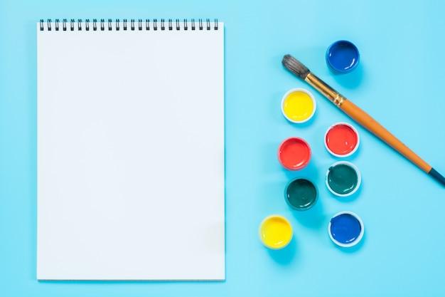 Di nuovo a scuola. pitture colorate, album e pennello su un blu incisivo. copia spazio. Foto Premium