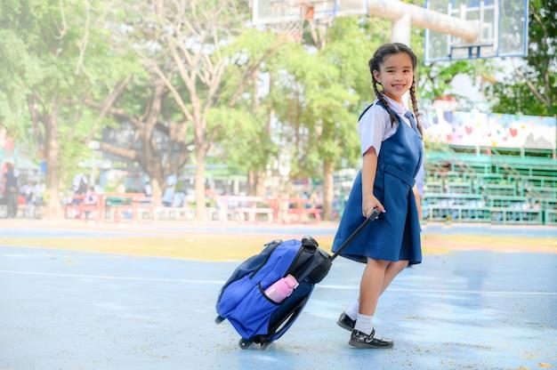 Di nuovo a scuola. ragazza sorridente felice dalla scuola elementare al cortile della scuola. Foto Premium