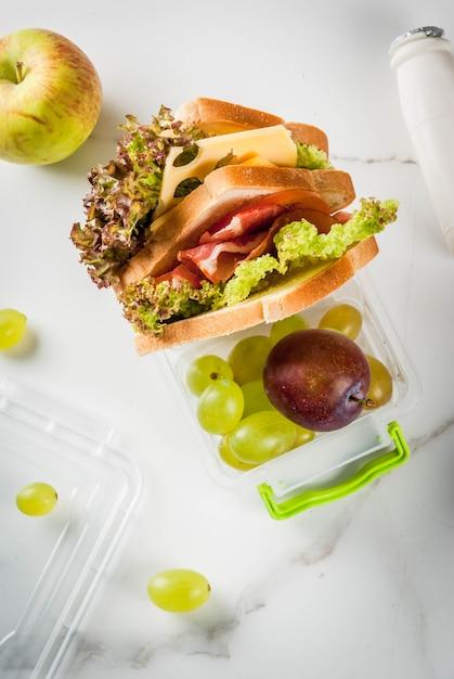 Di nuovo a scuola. un pranzo sano in una scatola è frutta fresca mele, prugne, uva, una bottiglia di yogurt e un panino con lattuga, pomodori, formaggio, carne. tavolo in marmo bianco. vista dall'alto Foto Premium