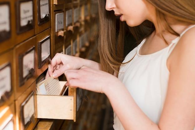 Di nuovo al concetto del banco con la fine in su della donna che studia nella libreria Foto Gratuite