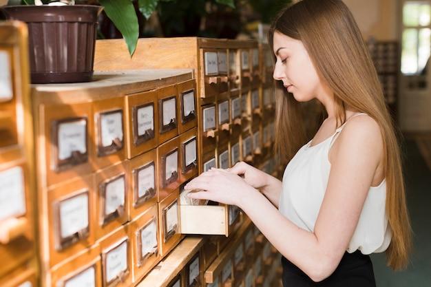 Di nuovo al concetto della scuola con la donna che studia nella biblioteca Foto Gratuite