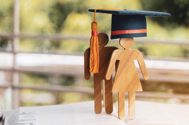 Di nuovo al concetto della scuola, la gente firma il legno con il cappuccio celebrante di graduazione sul libro di testo aperto con verde chiaro Foto Premium