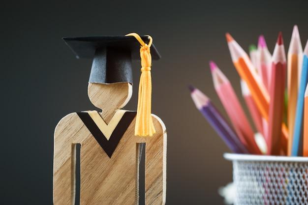 Di nuovo al concetto della scuola, la gente firma il legno con la scatola della matita della sfuocatura del cappuccio di celebrazione di graduazione Foto Premium