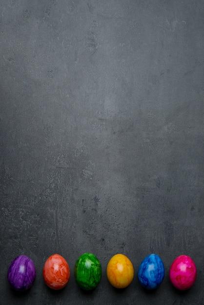 Di uova di pasqua dipinte colorate multi su un fondo di pietra scuro Foto Premium