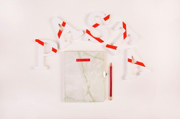 Diario e matita di marmo circondati dalla parola di pasta Foto Gratuite