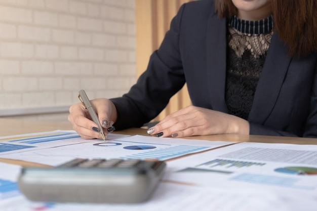 Dichiarazione del bilancio del rapporto finanziario della donna che lavora con i grafici dei documenti Foto Premium