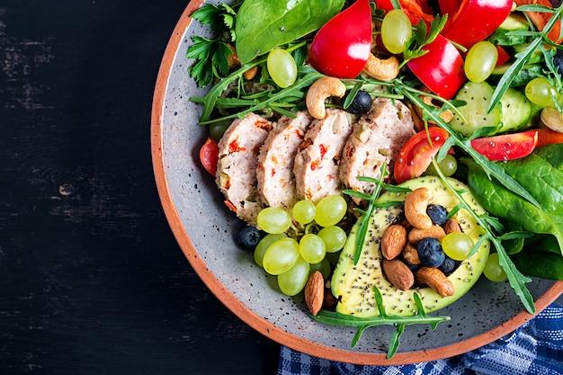 Dieta chetogenica. ciotola del buddha con polpettone, avocado, peperone dolce, pomodoro, cetriolo, bacche e noci. detox e concetto di ciotola superfoods sano. vista dall'alto, vista dall'alto, disteso Foto Premium