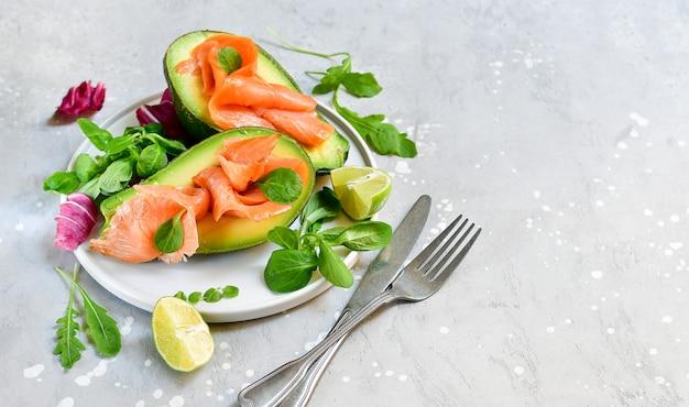 Dieta dietetica chetogenica salmone e insalata di avocado con rucola e lime. cibo cheto Foto Premium