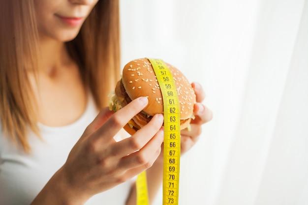 Dieta. giovane donna che le impedisce di mangiare cibo spazzatura. concetto di mangiare sano Foto Premium