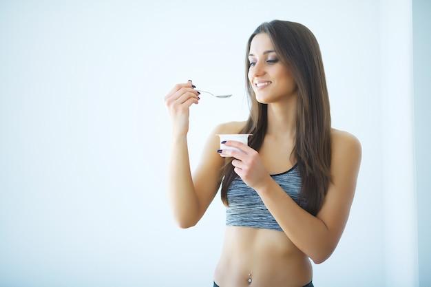 Dieta. giovane donna felice che mangia yogurt in cucina Foto Premium