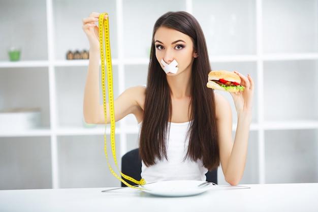 Dieta. la donna del ritratto vuole mangiare un hamburger ma ha bloccato la bocca di skochem, la dieta, il cibo spazzatura, la forza di volontà nella nutrizione Foto Premium