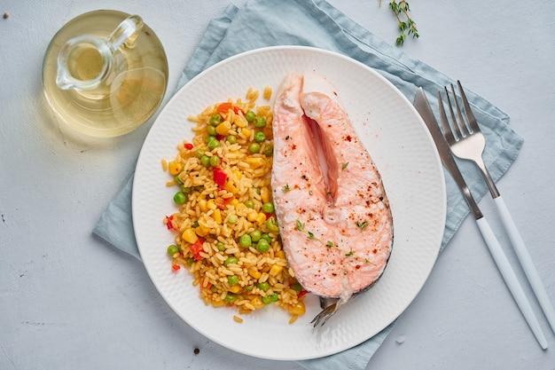 Dieta paleo, keto, fodmap. salmone al vapore e verdure, piatto bianco sul tavolo blu Foto Premium