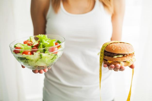 Dieta. peso corporeo di misurazione della donna sull'hamburger e sul salat della tenuta della bilancia. i dolci sono cibo spazzatura malsano. dieta, alimentazione sana, stile di vita. perdita di peso. obesità. Foto Premium