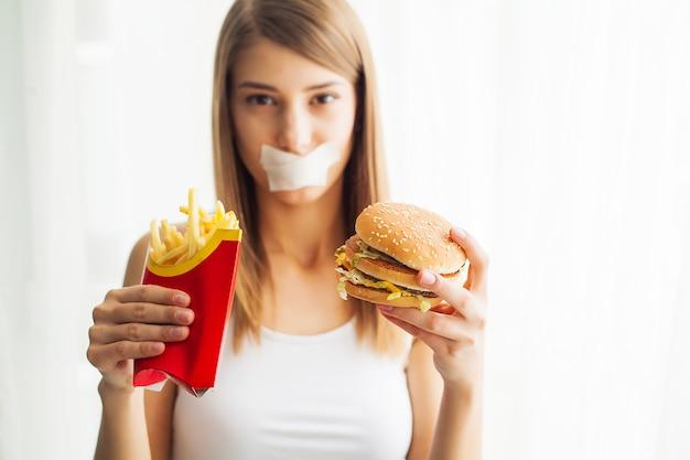 Dieta, ritratto donna vuole mangiare un hamburger ma bloccato bocca skochem, il concetto di dieta, cibo spazzatura, forza di volontà nella nutrizione Foto Premium