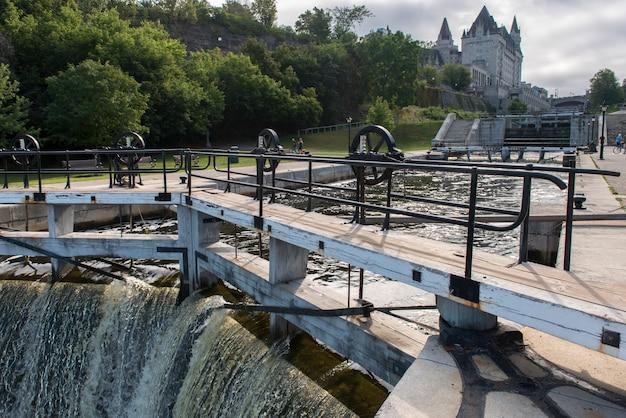 Diga sul canale rideau con parliament building sullo sfondo, parliament hill, ottawa, ontario, ca Foto Premium