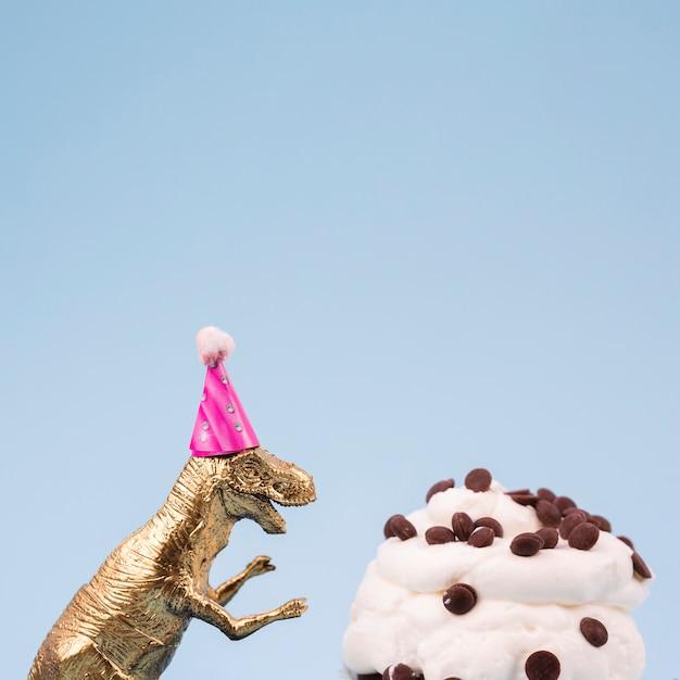 Dinosauro giocattolo e gustoso muffin Foto Gratuite