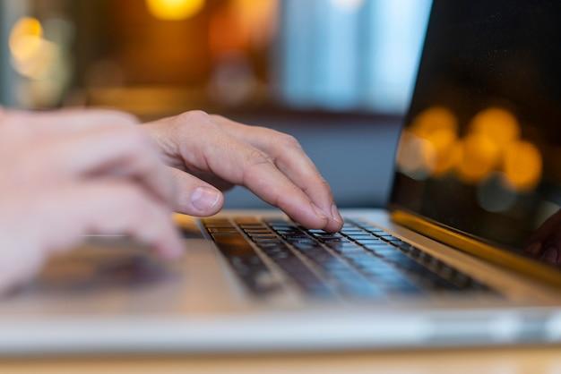 Dipendente che scrive sul computer portatile con bokeh Foto Gratuite